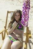 Flicka i bikinisammanträde på en strandstol arkivbilder