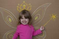 Flicka i bilden av feer med målade vingar och trollspösammanträde mot väggen Royaltyfri Foto