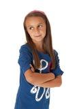 Flicka i blått som från sidan ser med hennes vikta armar Arkivfoton