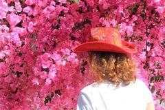 Flicka i cowboys hatt framme av rosa blommor arkivbilder
