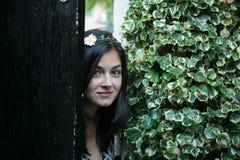 Flicka i dörren av en trädgård Arkivfoto