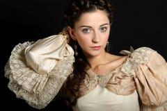 Flicka i den barocka klänningen som ser kameran arkivbild