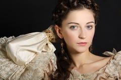 Flicka i den barocka klänningen som ser kameran arkivfoto