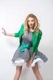 Flicka i den framkallande klänningen och det gröna omslaget Arkivfoto
