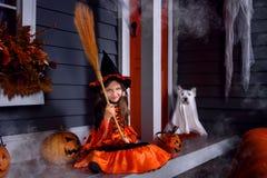 Flicka i den halloween dräkten med hunden royaltyfria foton