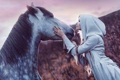 Flicka i den med huva kappan med hästen, effekt av royaltyfri bild