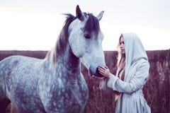 flicka i den med huva kappan med hästen, effekt av toningen royaltyfria foton