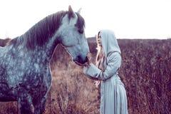 flicka i den med huva kappan med hästen, effekt av toningen royaltyfri fotografi
