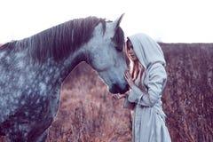 flicka i den med huva kappan med hästen, effekt av toningen arkivfoton
