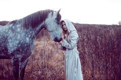 flicka i den med huva kappan med hästen, effekt av toningen royaltyfri foto