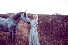 flicka i den med huva kappan med hästen, effekt av toningen arkivbild