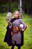 Flicka i den medeltida harnesken som rymmer en uggla Royaltyfri Foto