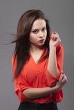 Flicka i den röda skjortan, grå bakgrund Glad kvinna för barnmodebrunett med hårrörelse arkivfoton