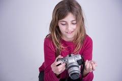 Flicka i den röda skjortan som rymmer den gamla kameran och att le arkivfoton