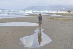 Flicka i den randiga t-skjortan som kör längs stranden fotografering för bildbyråer