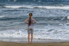 Flicka i den randiga t-skjortan som ser havet arkivfoton
