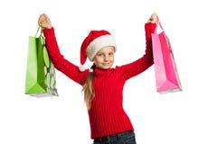 Flicka i den Santa Claus hatten med shoppingpåsar Royaltyfri Foto