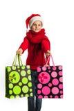 Flicka i den Santa Claus hatten med shoppingpåsar Arkivfoton