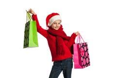 Flicka i den Santa Claus hatten med shoppingpåsar Arkivfoto