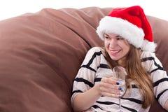 Flicka i den Santa Claus hatten och exponeringsglaset av champagne Fotografering för Bildbyråer