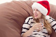 Flicka i den Santa Claus hatten och exponeringsglaset av champagne Royaltyfri Fotografi