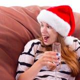 Flicka i den Santa Claus hatten och exponeringsglaset av champagne Royaltyfria Bilder