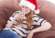Flicka i den Santa Claus hatten och exponeringsglaset av champagne Royaltyfri Foto