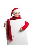 Flicka i den Santa Claus hatten som rymmer en affisch Arkivbilder