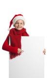 Flicka i den Santa Claus hatten som rymmer en affisch Royaltyfri Foto