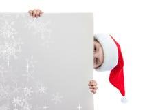 Flicka i den Santa Claus hatten som rymmer en affisch Royaltyfria Bilder