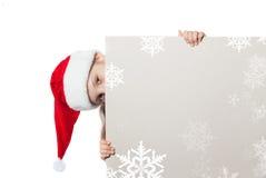 Flicka i den Santa Claus hatten som rymmer en affisch Royaltyfri Fotografi