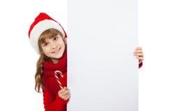 Flicka i den Santa Claus hatten som rymmer en affisch Arkivbild