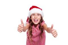 Flicka i den Santa Claus hatten som visar upp tum Royaltyfri Foto