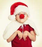 Flicka i den santa hatten med clownnäsan på isolerad vit Arkivfoton
