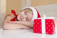 Flicka i den santa hatten som drömmer om feriegåvor Royaltyfri Fotografi