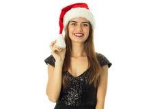 Flicka i den santa hatten som ser och ler på kamera Royaltyfri Foto