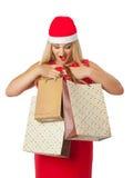 Flicka i den santa hjälpredahatten som ser shoppingpåsar Royaltyfri Bild