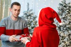 Flicka i den santa tröjan som ger en gåva till den stiliga grabben royaltyfria foton
