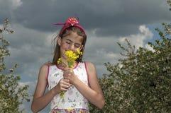 Flicka i den sura körsbärsröda fruktträdgården med den gula blomman Arkivbilder