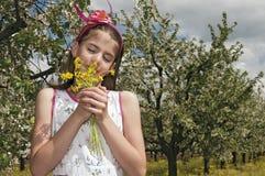 Flicka i den sura körsbärsröda fruktträdgården som luktar blommor Royaltyfri Fotografi