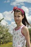 Flicka i den sura körsbärsröda fruktträdgården som ser trumpen Arkivfoton