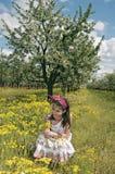 Flicka i den sura körsbärsröda fruktträdgården som squatting Royaltyfri Fotografi