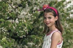 Flicka i den sura körsbärsröda fruktträdgården vid trädet Royaltyfri Foto