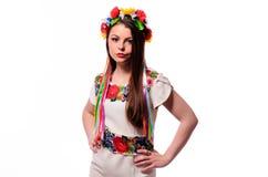 Flicka i den ukrainska nationella traditionella dräkten som rymmer hennes blommachaplet - som isoleras på vit royaltyfria foton