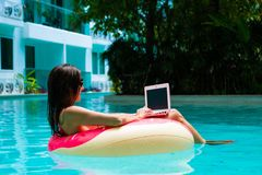 Flicka i den uppbl?sbara cirkeln i p?len med en b?rbar dator, begreppet av att frilansa och rekreation royaltyfri foto