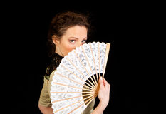 Flicka i den viktorianska klänningen som hinding bak en fan royaltyfri fotografi