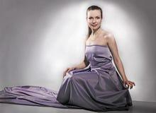 Flicka i den violetta klänningen Arkivbild