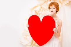 Flicka i den vita klänningen med röd hjärta i händer royaltyfri fotografi
