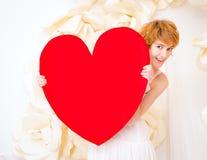 Flicka i den vita klänningen med röd hjärta i händer arkivbilder