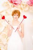 Flicka i den vita klänningen med röd hjärta i händer royaltyfri bild